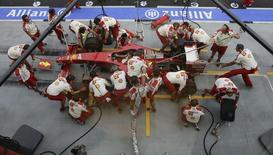 Crew members of the Ferrari Formula One team practise refuelling and pit stops prior to the start of the third practice session of the Singapore F1 Grand Prix at the Marina Bay street circuit September 26, 2009.  REUTERS/Tim Chong