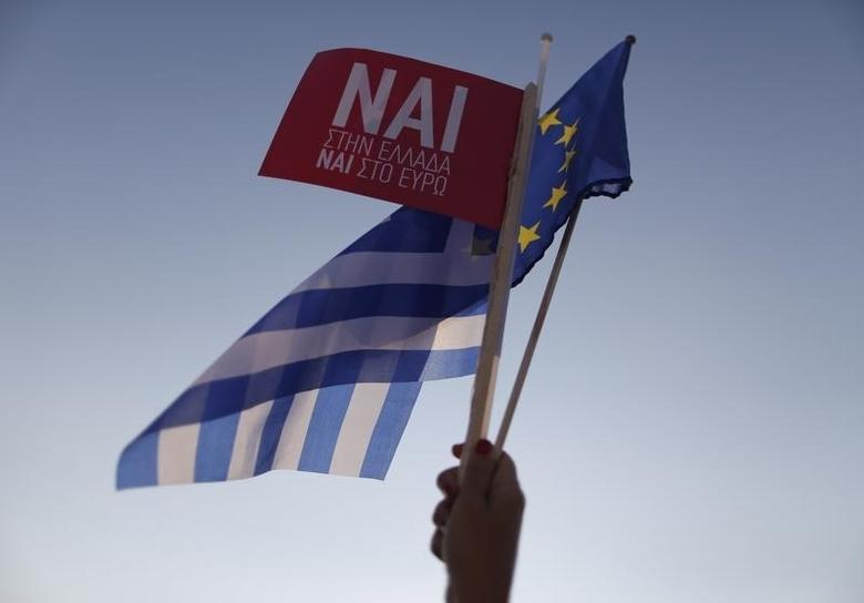 A 'Yes' supporter waves a Greek flag on arrival for the pro-Euro rally at the Panathenean stadium in Athens, Greece, July 3, 2015.    REUTERS/Christian Hartmann