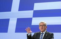 European Commission President Jean-Claude Juncker gives a statement while standing in front a giant Greek flag projected in the press room at the EU commission headquarters in Brussels, Belgium June 29, 2015.  REUTERS/Yves Herman