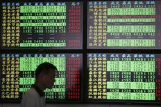 En la imagen, un inversor pasa junto a varias pantallas que muestran información bursátil en una fotografía tomada en Shangái, China, el 3 de julio de 2015.  Las 21 principales corredurías chinas dijeron el sábado que invertirían de forma colectiva al menos 120 millones de yuanes (19.300 millones de dólares) para ayudar a estabilizar los mercados financieros del país, después de una caída de casi el 30 por ciento desde mediados de junio. REUTERS/Aly Song