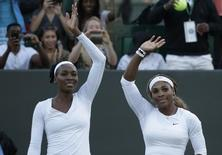 Venus Williams of the U.S. (L) and Serena Williams of the U.S.wave after defeating Oksana Kalashnikova of Georgia and Olga Savchuk of Ukraine in their women's doubles tennis match at the Wimbledon Tennis Championships, in London June 25, 2014.     REUTERS/Max Rossi