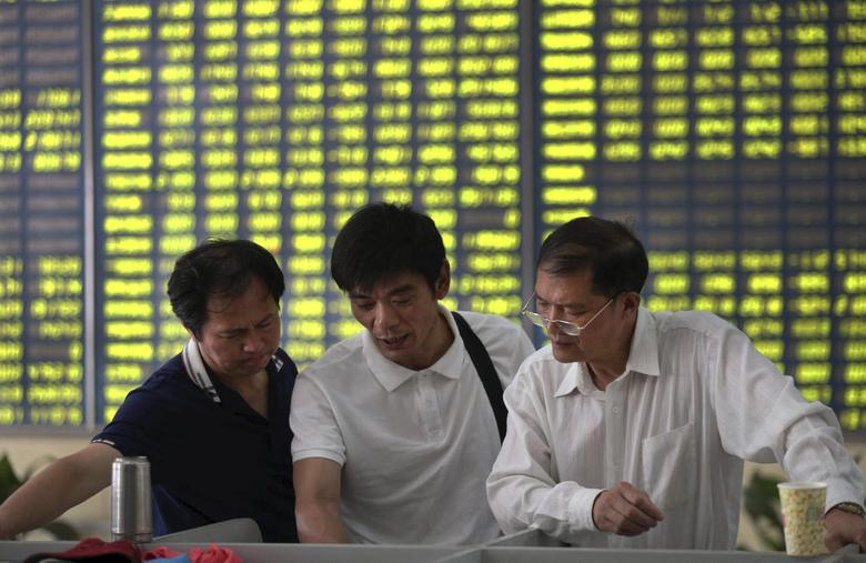 Investors talk in front of an electronic board showing stock information, filled with green figures indicating falling prices, at a brokerage house in Nantong, Jiangsu province, China, July 3, 2015. REUTERS/Stringer
