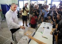 """Le ministre des Finances grec, Yanis Varoufakis, ici dans un bureau de vote d'Athènes, rencontrera les principaux banquiers du pays dans la soirée de dimanche, a dit à Reuters un représentant du ministère alors que des sondages d'opinion donnent une courte victoire du """"non"""" au référendum organisé par Athènes sur les propositions des créanciers internationaux. /Photo prise le 5 juillet 2015/REUTERS/Jean-Paul Pélissier"""