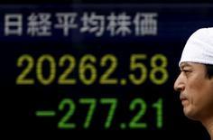 Un peatón camina junto a un tablero electrónico que muestra el índice Nikkei afuera de una agencia de la bolsa en Japón, 6 de julio de 2015. El índice Nikkei de la bolsa de Tokio cayó luego de que el resultado de un referendo en Grecia avivó el temor a que Atenas pueda verse obligada a abandonar el euro, poniendo más presión sobre la economía europea y la unión monetaria. REUTERS/Yuya Shino