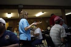Una mesera lleva platos en un restaurante en Boyou La Batre, Alabama. 10 de noviembre de 2009. La expansión del sector de servicios en Estados Unidos bajó por tercer mes consecutivo en junio, presionado por una desaceleración en el empleo y el crecimiento de la producción, mostró un reporte de la industria el lunes. REUTERS/Carlos Barria