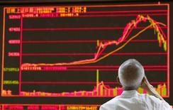 Un hombre observa un gráfico con acciones en una correduría en Pekín, jul 6 2015. La bolsa de futuros financieros de China dijo el lunes que limitará las transacciones diarias con los derivados del índice accionario CSI 500 y que fortalecerá la supervisión del uso de los futuros de índices en coberturas, para calmar a un mercado volátil.   REUTERS/Kim Kyung-Hoon
