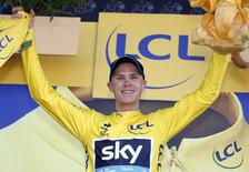 Team Sky rider Chris Froome of Britain celebrates as he wears the race leader's yellow jersey on the podium of the third stage of the 102nd Tour de France cycling race from Anvers to Huy, July 6, 2015.  REUTERS/Eric Gaillard