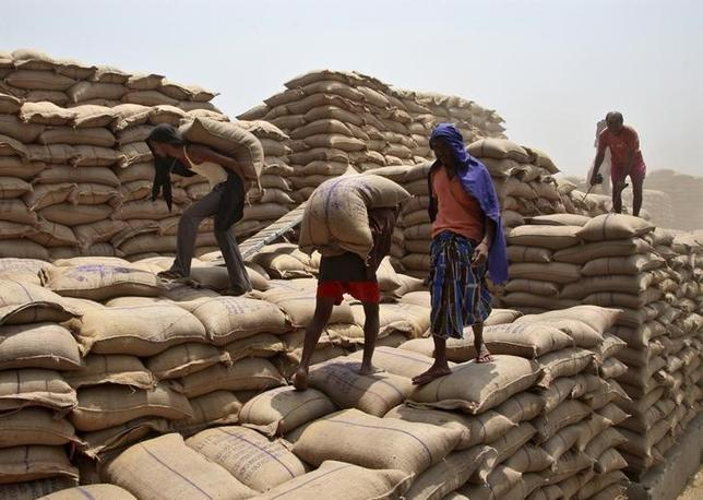 Labourers unload sacks filled with wheat from a truck at the Punjab State Civil Supplies Corporation Limited (PUNSUP) godown at a wholesale grain market in Punjab, May 6, 2015. REUTERS/Ajay Verma/Files