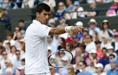 Novak Djokovic of Serbia requests his towel from a ball girl during his match against Kevin Anderson of South Africa at the Wimbledon Tennis Championships in London, July 7, 2015. REUTERS/Suzanne Plunkett