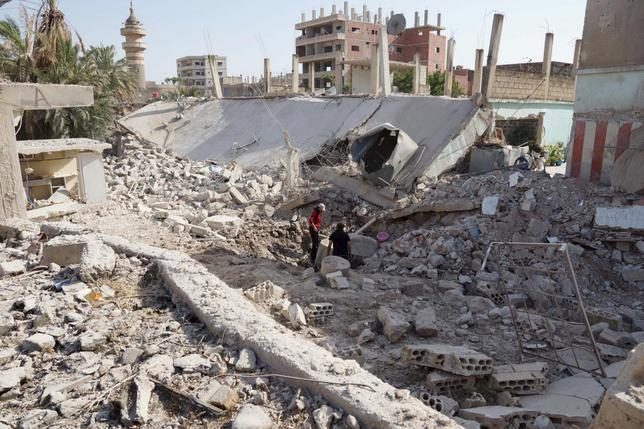 Residents inspect damage from what activists said were barrel bombs dropped by forces loyal to Syria's President Bashar Al-Assad in Tafas town in Daraa, Syria, July 2, 2015. REUTERS/Alaa Al-Faqir
