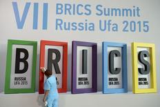 Рабочий моет постер с перед началом саммита БРИКС в Уфе 7 июля 2015 года.  Россия, Бразилия, Индия, Китай и Южно-Африканская Республика не обсуждали создание валютного союза, сказал министр финансов РФ Антон Силуанов. REUTERS/BRICS Photohost/RIA Novosti