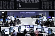 Traders are pictured at their desks in front of the DAX board at the Frankfurt stock exchange July 7, 2015. REUTERS/Staff/remote