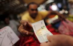 Un vendedor recibe un billete de cinco euros de un cliente en el mercado central de Atenas, jul 8 2015. Grecia estaría a punto de convertirse en el primer país en abandonar la zona euro, según un sondeo de Reuters que por primera vez coloca la probabilidad de que la unión monetaria se desarme en más del 50 por ciento. REUTERS/Christian Hartmann