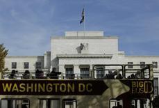 Туристический автобус проезжает мимо здания ФРС США в Вашингтоне 28 октября 2014 года. Регуляторы ФРС хотят увидеть больше доказательств укрепления экономики США, прежде чем повышать ключевую ставку, говорится в протоколе июньского заседания Центробанка, при этом кризис в Греции был назван серьезной проблемой.  REUTERS/Gary Cameron  (