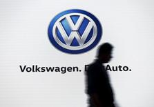 A man walks past a screen displaying a logo of Volkswagen at an event in New Delhi, India, June 23, 2015. REUTERS/Anindito Mukherjee