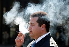 Una persona fumando un cigarrillo en una calle de Valparaíso, Chile, mayo 31 2010. La unidad de la internacional British American Tobacco (BAT) en Chile dijo el jueves que cerrará varias plantas que posee en el país, luego de que el Congreso aprobó el endurecimiento de una ley antitabaco que afectará negativamente sus negocios. REUTERS/Eliseo Fernandez