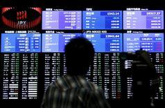 Una persona filma un tablero electrónico que muestra el índice Nikkei de Japón, en una correduría en Tokio, Japón, 9 de julio de 2015. El índice Nikkei de la bolsa de Tokio bajó el viernes, debilitado por las fuertes pérdidas en las acciones de Fast Retailing Co tras su débil pronóstico de ventas nacionales para el trimestre actual. REUTERS/Yuya Shino