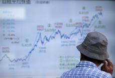 Мужчина у брокерской конторы в Токио. 13 июля 2015 года. Фондовый рынок Китая вырос в понедельник третий день подряд, вызвав подъем на других рынках Азии и дав инвесторам надежду, что принятые правительством меры спасли рынок от краха. REUTERS/Issei Kato