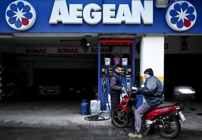A man (R) refuels his motorcycle at an Aegean Oil gas station in Athens February 10, 2015. REUTERS/ Alkis Konstantinidis