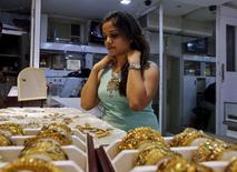 Женщина примеряет золотое ожерелье на рынке в Мумбаи. 8 июля 2015 года. Цены на золото снижаются, поскольку после соглашения Греции с кредиторами инвесторы вспомнили о предстоящем повышении процентных ставок ФРС, которое будет неблагоприятным для рынка золота. REUTERS/Shailesh Andrade