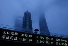 Foto de archivo de un hombre caminando junto a un tablero electrónico que muestra los índices de Shanghái y de Shenzhen, en el distrito financiero de Pudong, en Shanghái, 26 de junio de 2015. El banco central de China dijo el martes que el sistema financiero del país se mantenía básicamente estable y que seguiría una política monetaria prudente, aunque también reduciría los costos de endeudamiento y aumentaría la porción de financiamiento directo en la financiación social. REUTERS/Aly Song/FIles