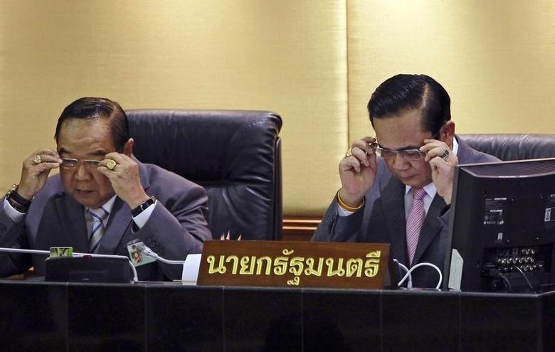 Thailand's Prime Minister Prayuth Chan-ocha (R) and Deputy Prime Minister and Defence Minister Prawit Wongsuwan don glasses before Prayuth reads out his government's policy, at the Parliament in Bangkok September 12, 2014. REUTERS/Chaiwat Subprasom