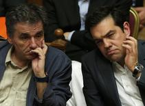 Greek Prime Minister Alexis Tsipras (R) sits next to Finance Minister Euclid Tsakalotos (L) as he attends a parliamentary session in Athens, Greece July 15, 2015. REUTERS/Alkis Konstantinidis
