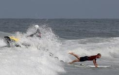 Mick Fanning (R) of Australia dives from a jet ski during the men's World Surf League (WSL) championship at Barra da Tijuca beach in Rio de Janeiro May 15, 2015. REUTERS/Sergio Moraes