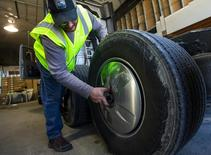 A technician installs an aerodynamic hubcap to a transport truck at Hirschbach Motor Lines in East Dubuque, Illinois, United States, April 30, 2015.  REUTERS/Jim Young