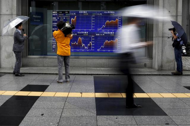 Videographer films an electronic board showing the graphs of exchange rates between the Japanese yen, the U.S. dollar and Euro outside a brokerage in Tokyo, Japan, July 6, 2015. REUTERS/Yuya Shino