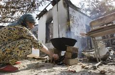 Этническая узбечка готовит на открытом огне у сожженного дома в Оше 29 июня 2010 года. Америка предупредила Киргизию в понедельник, что от эскалации напряженности в отношениях могут пострадать множество финансируемых США программ для бедной центральноазиатской страны. REUTERS/Shamil Zhumatov