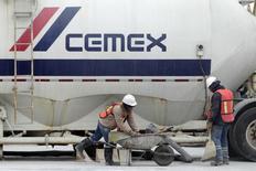 Trabajadores frente a un camión en una planta de concreto de la cementera mexicana CEMEX, en Monterrey, 24 de febrero de 2015. La mexicana Cemex, una de las mayores cementeras del mundo, reportaría un desplome en su utilidad neta del segundo trimestre, mientras que sus ingresos se habrían visto golpeados por la volatilidad de las monedas de los mercados donde opera. REUTERS/Daniel Becerril