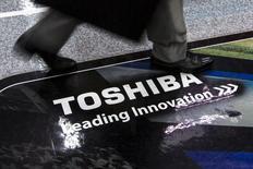 Мужчина проходит мимо логотипа  Toshiba Corp в магазиен в Токио 21 июля 2015 года. Японская Toshiba Corp сообщила в среду о завершении сделки по продаже 4,6 процента финского производителя подъемной техники и лифтов Kone Oyj примерно за 864,7 миллиона евро ($945,6 миллиона). REUTERS/Thomas Peter