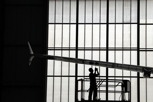 A worker uses a drill to screw bolts into the wing of an A320 plane that is under construction at the Airbus factory located in the northern Chinese city of Tianjin September 14, 2010.  REUTERS/David Gray
