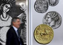 A man walks past pictures of ancient coins in central Athens, Greece, July 13, 2015.   REUTERS/Jean-Paul Pelissier
