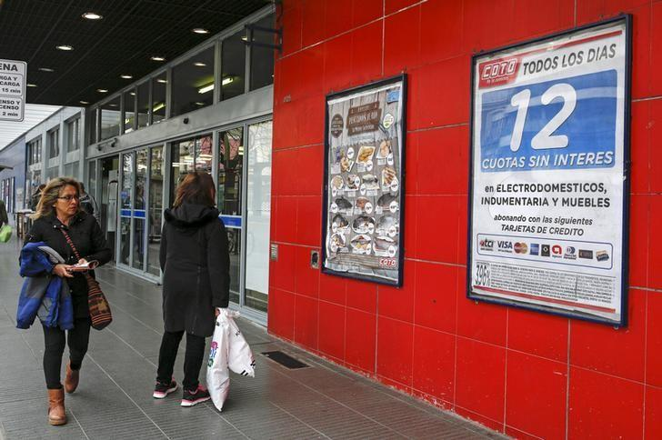 People look at posters offering a credit program allowing payment in 12 interest-free installments plasted on a supermarket wall in Buenos Aires, Argentina June 22, 2015. REUTERS/Agustin Marcarian