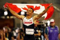 Jul 22, 2015; Toronto, Ontario, CAN; Andre De Grasse of Canada celebrates after winning the men's athletics 100m final during the 2015 Pan Am Games at CIBC Pan Am Athletics Stadium. Mandatory Credit: Erich Schlegel-USA TODAY Sports