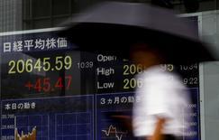 Un hombre camina junto a un tablero que muestra el índice Nikkei en Tokio, 17 de julio de 2015. Las bolsas de Asia bajaban el jueves luego de que el reporte de unos datos regionales dispares y unas caídas en Wall Street llevaron a los inversores a recoger ganancias, mientras el dólar se fortalecía tras el reporte de unas ventas sólidas de casas en Estados Unidos. REUTERS/Thomas Peter
