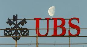 The waning moon is seen behind a logo of Swiss bank UBS in Zurich February 10, 2015. REUTERS/Arnd Wiegmann
