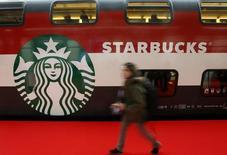 Женщина проходит мимо логотипа Starbucks на вокзале в Цюрихе 14 ноября 2013 года. Starbucks Corp сообщила о росте квартальной прибыли, поскольку новая еда, напитки и технологии помогли крупнейшей в мире сети кофеен привлечь больше покупателей. REUTERS/Arnd Wiegmann