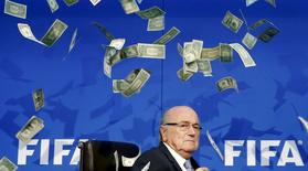 FIFA President Sepp Blatter reacts to banknotes thrown at him by British comedian known as Lee Nelson (unseen) while arriving for a news conference after the Extraordinary FIFA Executive Committee Meeting at the FIFA headquarters in Zurich, Switzerland July 20, 2015. REUTERS/Arnd Wiegmann