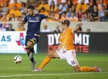Jul 25, 2015; Houston, TX, USA; Los Angeles Galaxy midfielder Sebastian Lletget (17) advances the ball during the first half as Houston Dynamo defender David Horst (18) defends at BBVA Compass Stadium. The Dynamo defeated the Galaxy 3-0. Mandatory Credit: Troy Taormina-USA TODAY Sports