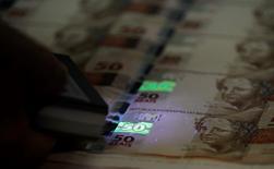 Funcionário verifica folhas de papel-moeda na Casa da Moeda. 23/08/2012 REUTERS/Sergio Moraes