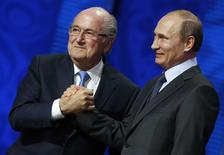 FIFA's President Sepp Blatter shakes hands with Russia's President Vladimir Putin (R) during the preliminary draw for the 2018 FIFA World Cup at Konstantin Palace in St. Petersburg, Russia July 25, 2015. REUTERS/Grigory Dukor - RTX1LRWK