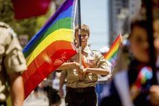 El boy scout Casey Chambers porta una bandera de arcoiris durante el festival del Orgullo Gay en San Francisco, California, el 29 de junio de 2014. La organización de los Boy Scouts de América levantó el lunes su prohibición a los líderes y empleados abiertamente gays, dando marcha atrás a una política que ha divido profundamente a la organización con sede en Texas y 105 años de historia. REUTERS/Noah Berger