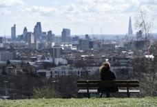 A woman looks towards the City of London financial district from Parliament Hill in north London March 31, 2015. REUTERS/Toby Melville