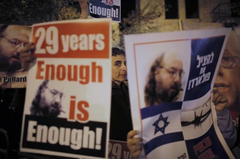 Israelis hold placards depicting Jonathan Pollard during a protest calling for his release from a U.S. prison, outside U.S. Secretary of State John Kerry's hotel in Jerusalem January 2, 2014. REUTERS/Ammar Awad