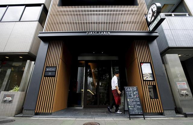 A man walks near the entrance of First Cabin hotel, which was converted from an old office building, in Tokyo, July 3, 2015. REUTERS/Toru Hanai