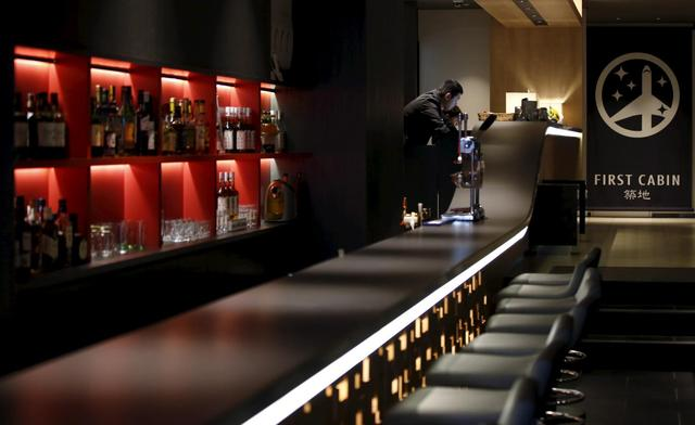 People stand at the front desk near a bar at First Cabin hotel, which was converted from an old office building, in Tokyo, July 3, 2015. REUTERS/Toru Hanai