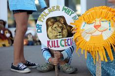 Piper Hoppe, 10, from Minnetonka, Minnesota, holds a sign at the doorway of River Bluff Dental clinic in protest against the killing of a famous lion in Zimbabwe, in Bloomington, Minnesota July 29, 2015. A Zimbabwean court on Wednesday charged a professional local hunter Theo Bronkhorst with failing to prevent an American from unlawfully killing 'Cecil', the southern African country's best-known lion. The American, Walter James Palmer, a Minnesota dentist who paid $50,000 to kill the lion, has left Zimbabwe. He says he did kill the animal but believed the hunt was legal and that the necessary permits had been issued. REUTERS/Eric Miller
